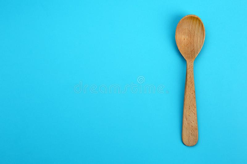 Clean empty wooden spoon on blue background, top view. Space. For text royalty free stock photo