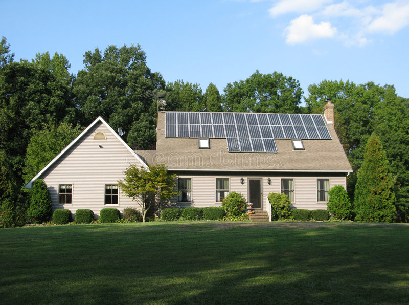 Clean Energy. A beautiful house with solar panels on the roof stock photography