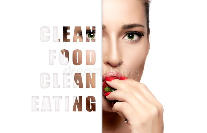 Clean food. Clean eating concept. Beautiful young woman eating fresh ripe strawberry royalty free stock images