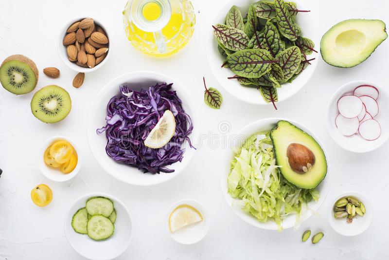 Clean food. Fresh raw vegetables and lettuce leaves to prepare a healthy snack meal salad. Top view. On a light royalty free stock photo