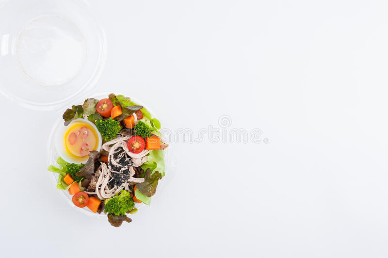 Clean food lunch box. Chicken breast salad with honey thyme sauce cooked by clean food concept in lunch box on white table royalty free stock images