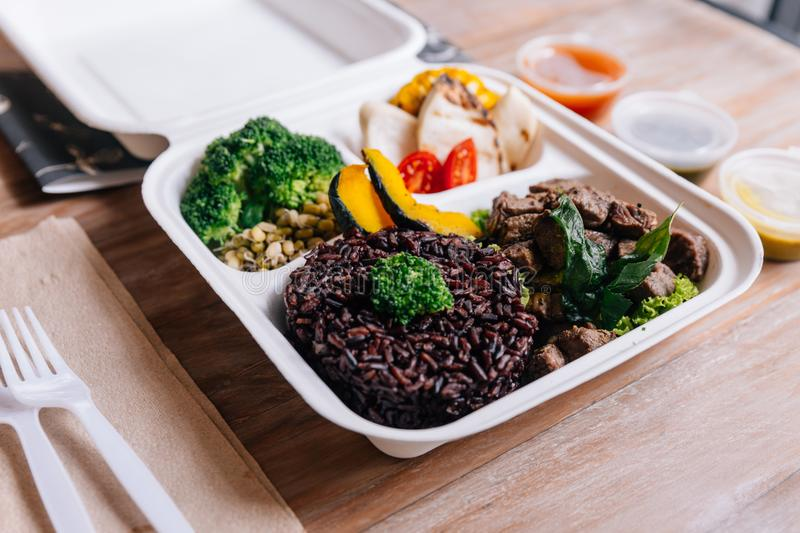 Clean food meal box: Diced grilled beef served with rice berry, broccoli, bean sprout, corn, mushroom and tomato.  royalty free stock photography