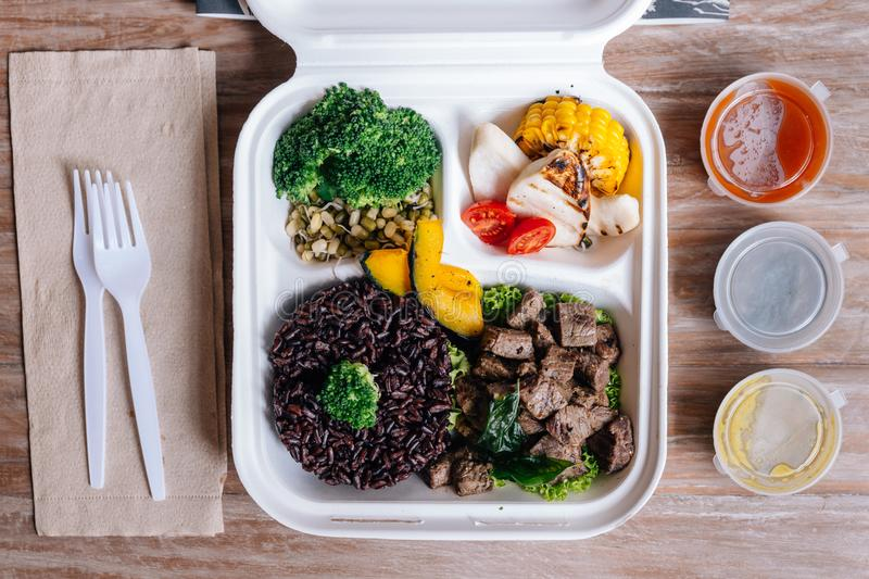 Clean food meal box: Diced grilled beef served with rice berry, broccoli, bean sprout, corn, mushroom and tomato.  stock photos