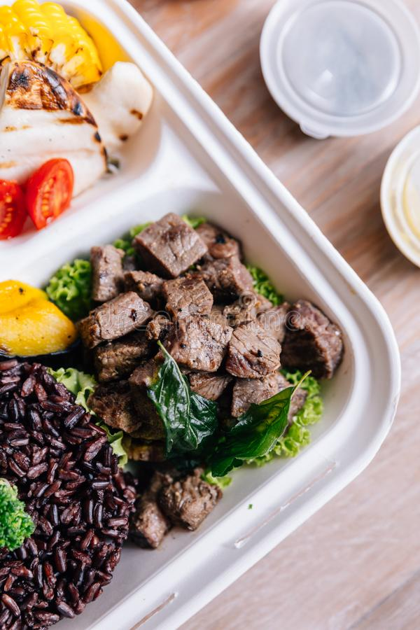 Clean food meal box: Diced grilled beef served with rice berry, broccoli, bean sprout, corn, mushroom and tomato. Clean food meal box: Diced grilled beef served royalty free stock images
