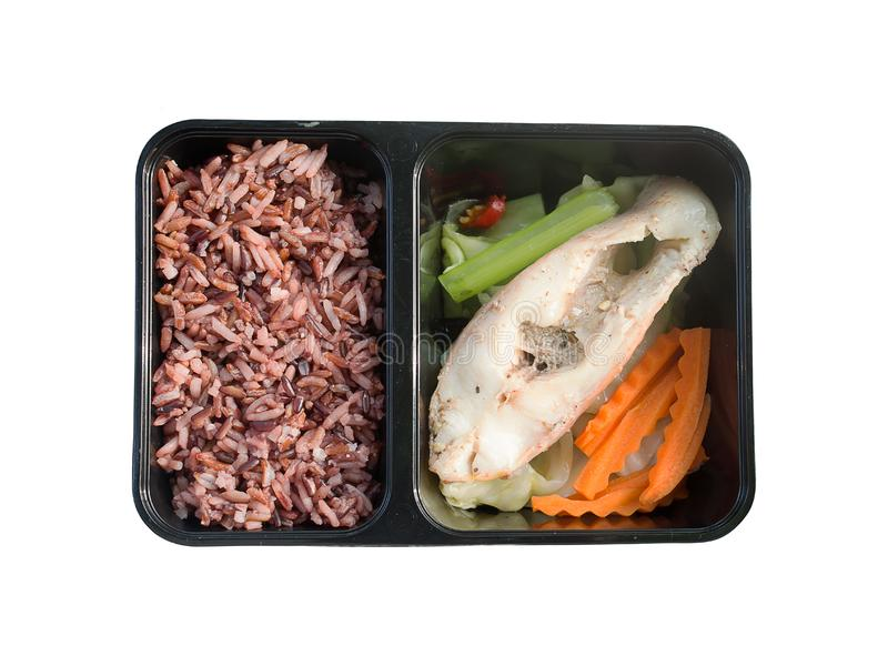 Clean food meal good for health and for diet. Brown rice with steamed fish and vegetable, carrot in black box. Lunch box isolated on white background stock photography
