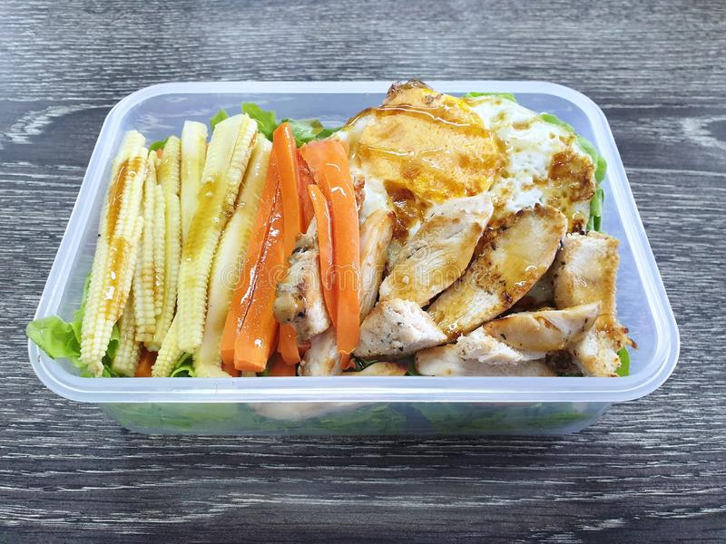 Clean food style, Top view of grilled chicken, fried egg and vegetable salad with carrot, lettuce and baby corn in lunch box royalty free stock photos