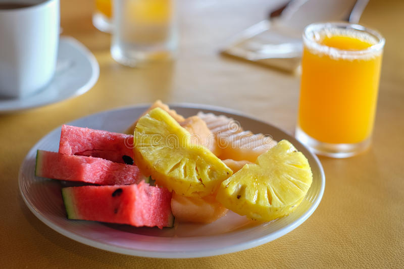 Clean food. Watermelon pineapple and orange juice yellow background stock photography