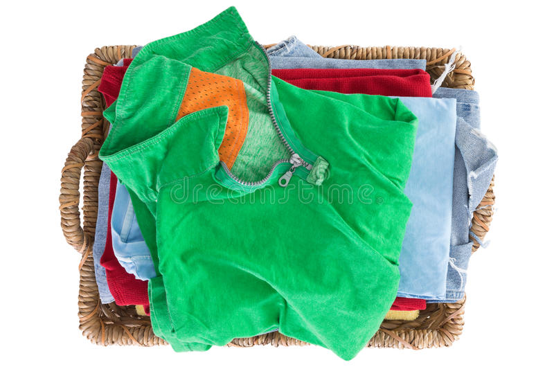 Clean fresh washed summer clothes in a basket. Neatly folded and viewed from above with a colorful green shirt on top of the pile, overhead close up view stock photo