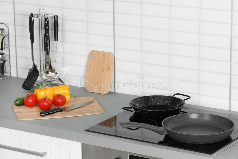 Clean frying pans and board with fresh vegetables stock images