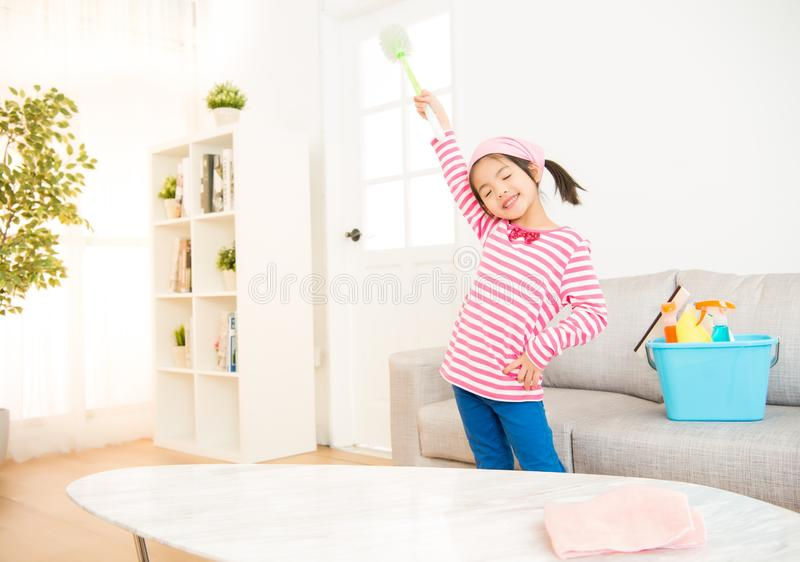 Clean girl having fun during spring cleaning. Clean little girl having fun during spring cleaning. Funny kids cleaning wearing pink top singing into broom stock image