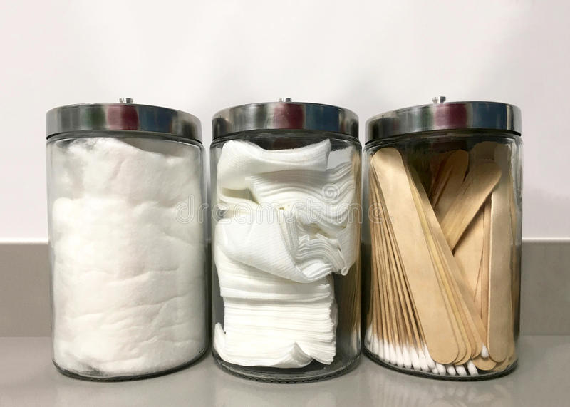 Clean glass jars with first aide supplies. Three glass jars on medical office counter with non-sterile q-tips, tongue depressors, 4x4`s and cotton ready for use royalty free stock photos