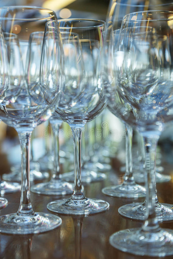 Clean glasses on a table prepared by the bartender for champagne and wine. Several of transparent glasses on a rack. Catering for the event preparation, clean stock photo