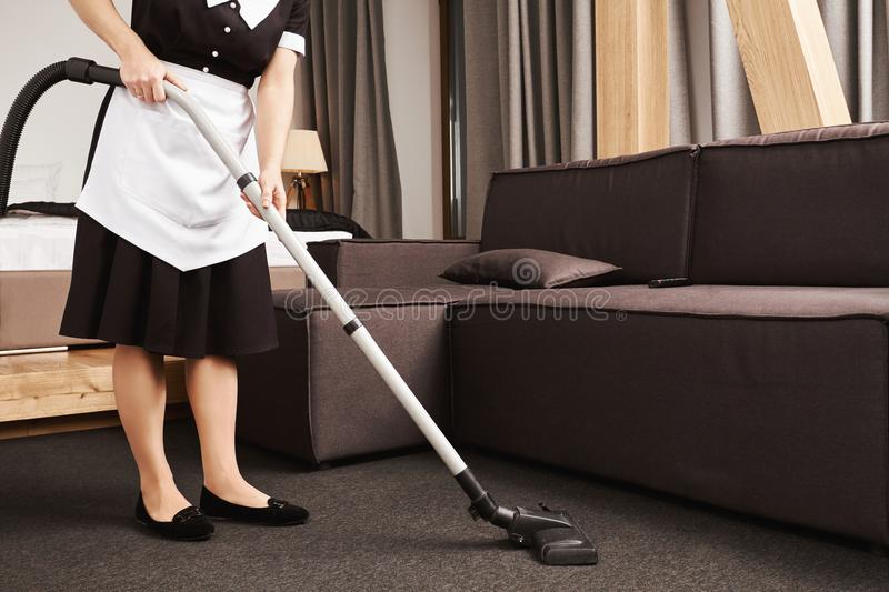 Clean house is key for productivity. Cropped shot of housemaid during work, cleaning living room with vacuum cleaner. Removing dirt and mess near sofa. Maid is royalty free stock photos
