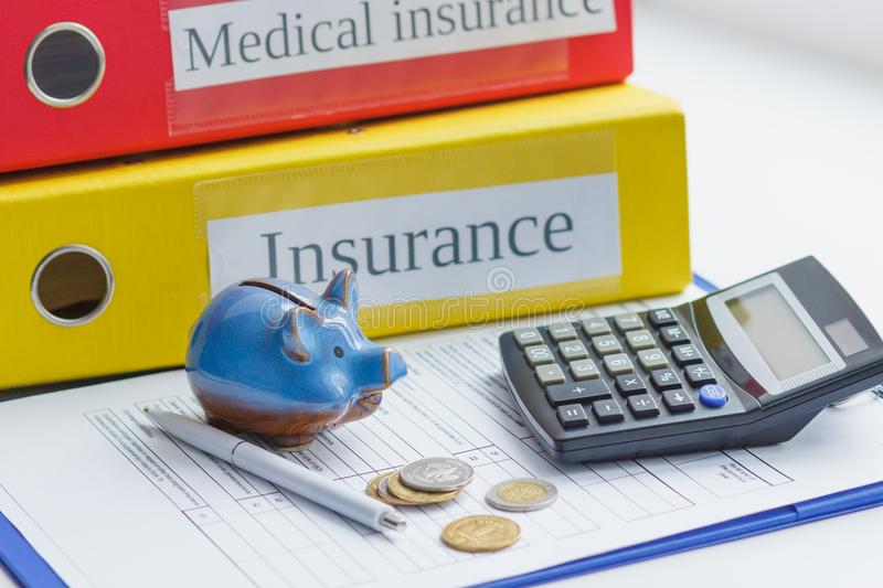 Clean insurance form, piggy bank, pen and coins stock photography