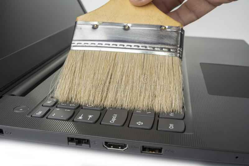 Clean keyboard with a wide brush from dust.  stock photography