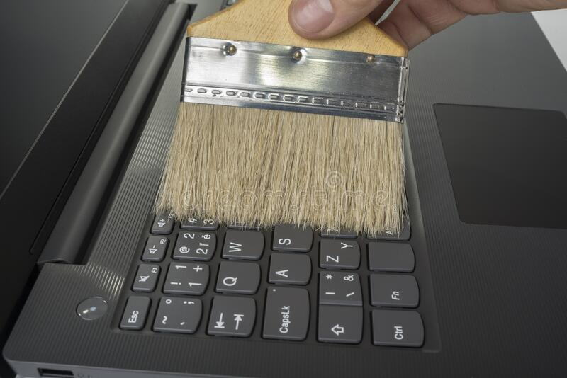 Clean keyboard with a wide brush from dust.  stock photo