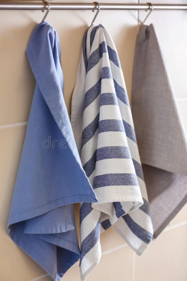 Clean kitchen towels hanging on rack stock photography