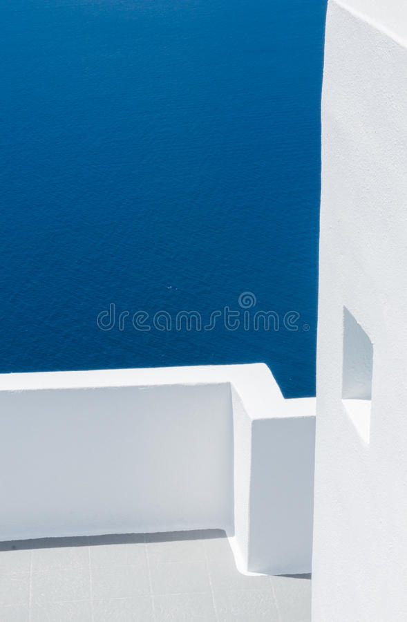 Greek Architecture with white walls. Greek architecture on the island of Santorini with white washed walls and the blue sea in the background stock image