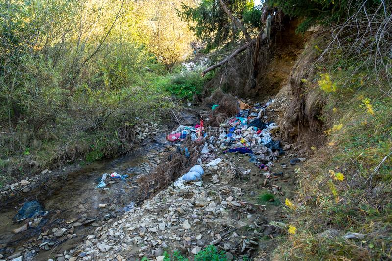 Clean little creek polluted with human trash, conceptual image of human negligence. Bancu, Romania- 08 October 2018: Clean little creek polluted with human stock photo