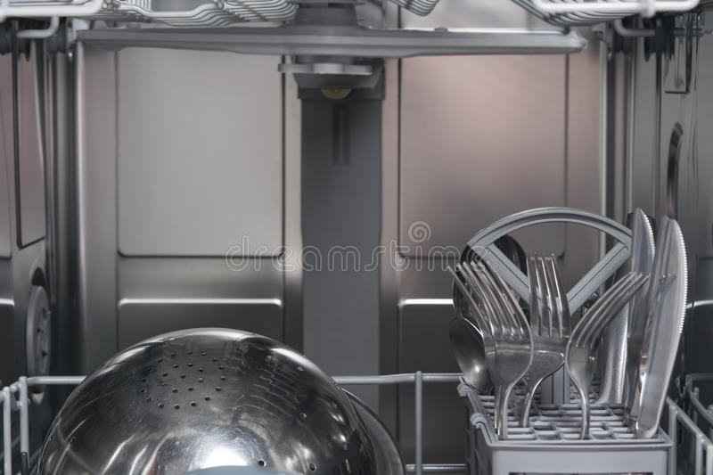 Clean metal cutlery, against the back wall of the dishwasher, with space for an inscription royalty free stock photos
