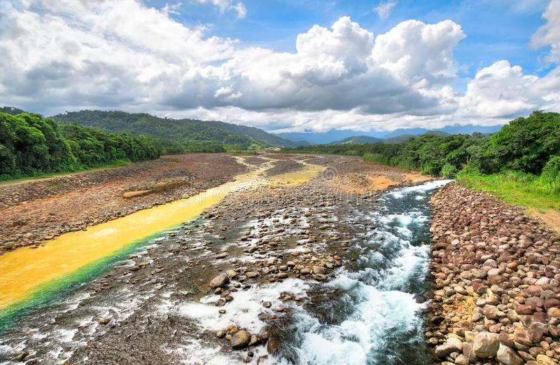 Clean and murky rivers converge in Costa Rica. A clean stream converges with the Rio Sucio near Guapiles, Costa Rica stock image