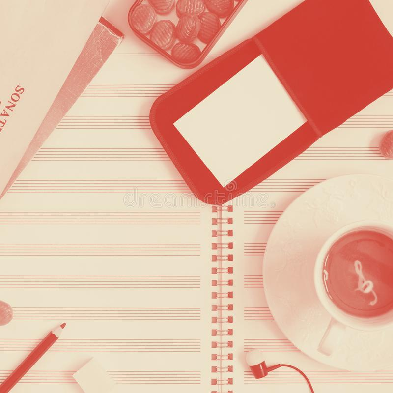 Clean music sheet, closed notes, pencil, metal box of sugar candies, glasses, case with two mockup business cards, head stock images