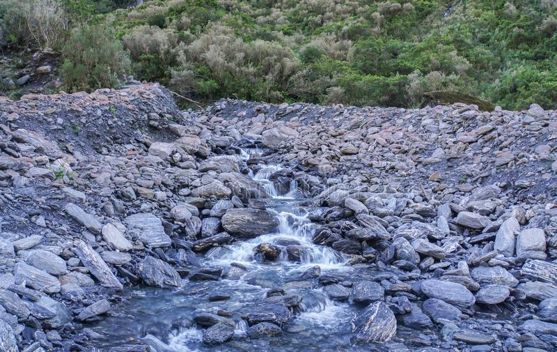 Natural waterway through stone heaps. Clean natural waterway through stone heaps royalty free stock photography