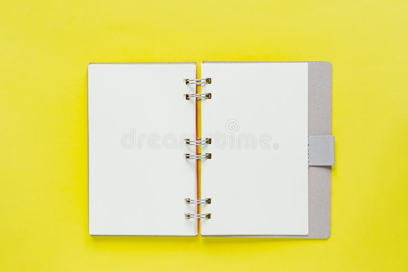 Clean note book for goals and resolutions in recycling paper cover. mockup for your design. Spiral note book on yellow background stock photos
