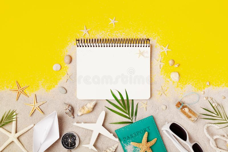 Clean notebook with accessories on yellow table top view. Planning summer holidays, travel and vacation background. Flat lay style stock photo