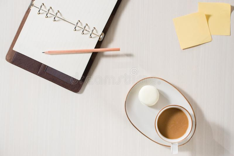 Clean notebook, cup of coffee and colorful macaron on gray desk top view. Cozy morning breakfast. Fashion flat lay. Sweet macarons stock photography