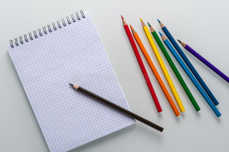 Clean notepad in a cage with a pencil lying on it and rainbow color pencils on a white background top view copy space. Art royalty free stock photos