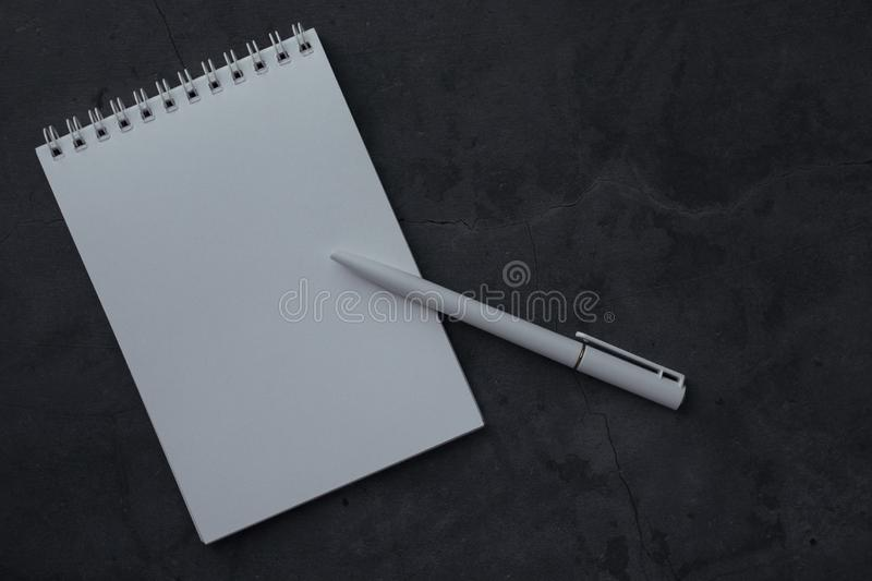 Clean notepad and pen on dark background with texture. Concept for education or business with space for text. Notebook with white paper for writing notes, top stock images