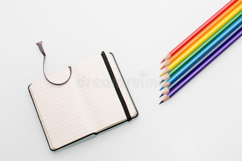 Clean notepad and rainbow color pencils in the shape of an arrow on a white background top view copy space. Art stock photo