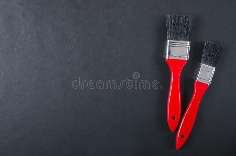 Clean paint brushes on the dark surface.Empty space for design. Close up of two clean paint brushes on the dark surface.Red handle and black bristle. Tools for stock photo