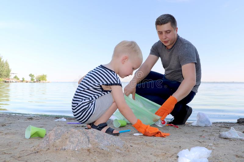 A small child collects trash on the beach. His dad points his finger where to throw garbage. Parents teach children cleanliness. stock photo