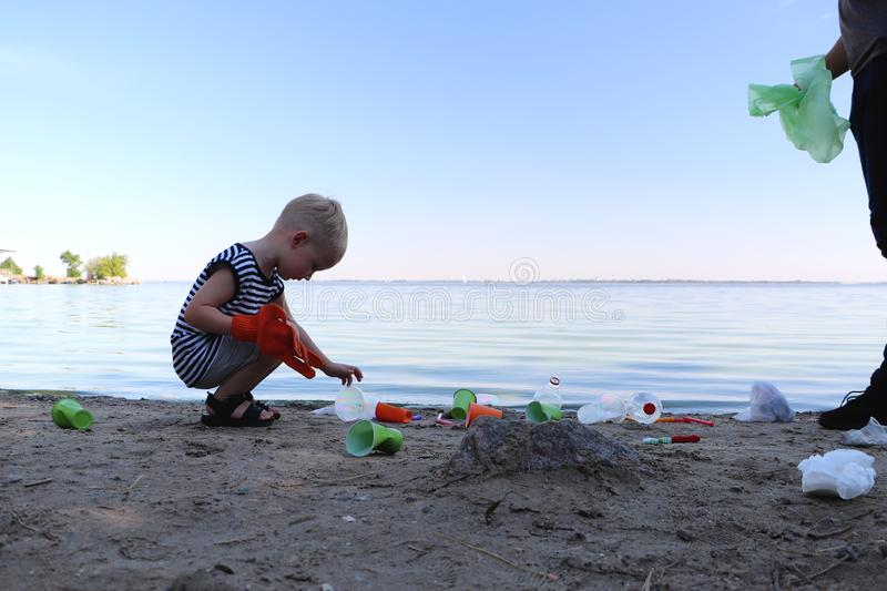 A small child collects trash on the beach. His dad points his finger where to throw garbage. Parents teach children cleanliness. royalty free stock images