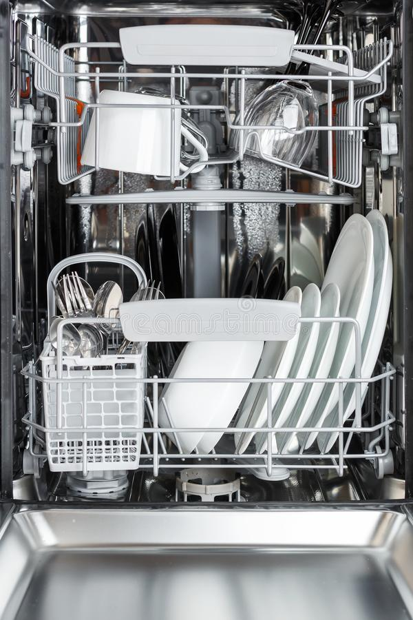 Clean plates, cups, glasses and cutlery in the dishwasher after royalty free stock image