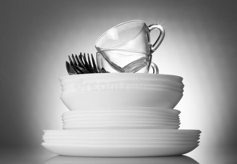 Clean plates and cutlery on bright beautiful gray background stock photography