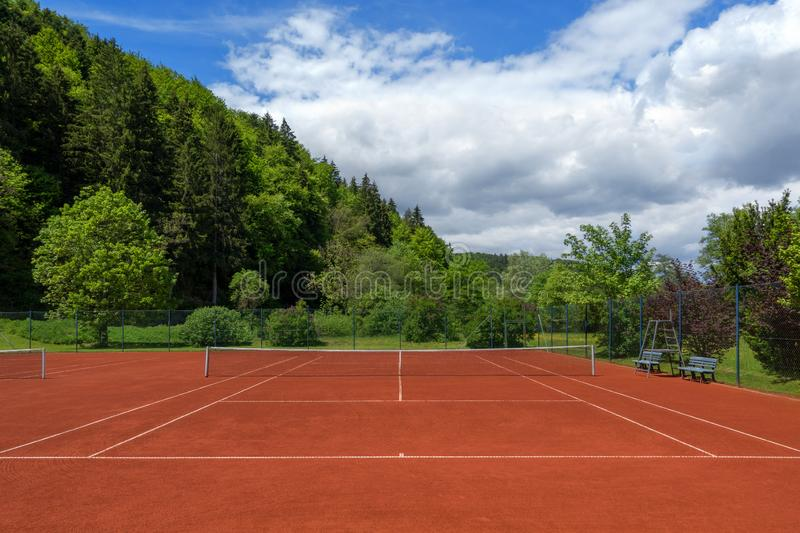 Clean pulled tennis court after the spring overhaul. Clean pulled tennis court with red sand after the spring overhaul stock photography
