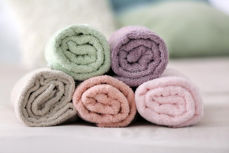 Clean rolled towels on bed in room stock images
