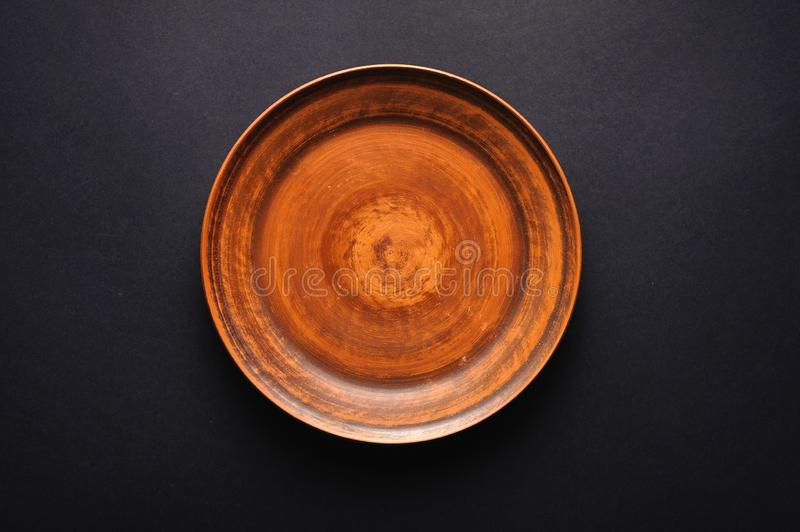Clean rustic plate on black background top view.  stock images