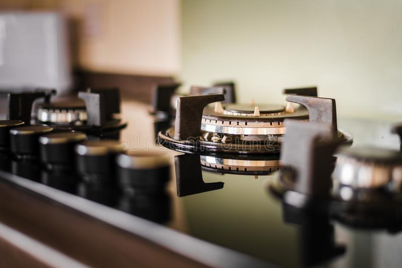 A clean and shiny cooker hob and knobs. Taken inside with golden light shining on the appliance stock photo