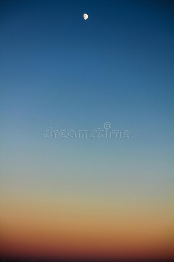 Clean sky during sunset with spectacular shades and the moon stock photo