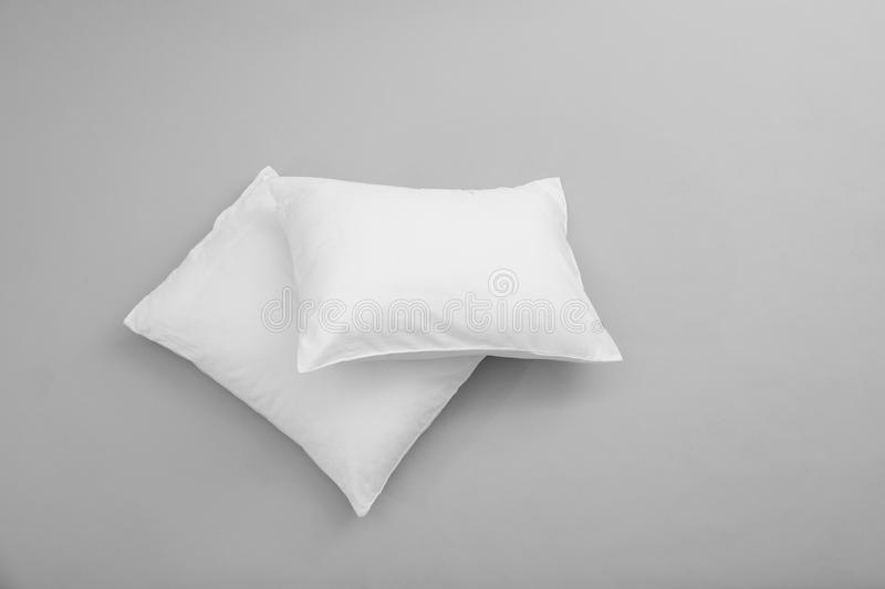 Clean soft bed pillows on grey background stock images