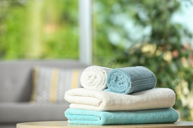 Clean soft terry towels on table indoors. Space for text stock image