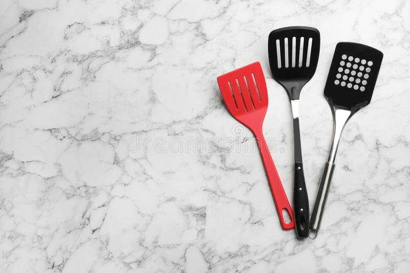 Clean spatulas on marble background, flat lay. Space for text stock photo