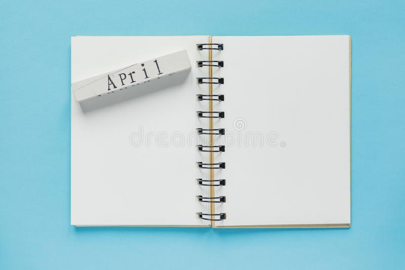 Clean spiral note book for notes and messages and april wooden calendar bar on blue background. Minimal business flat lay.  royalty free stock photo