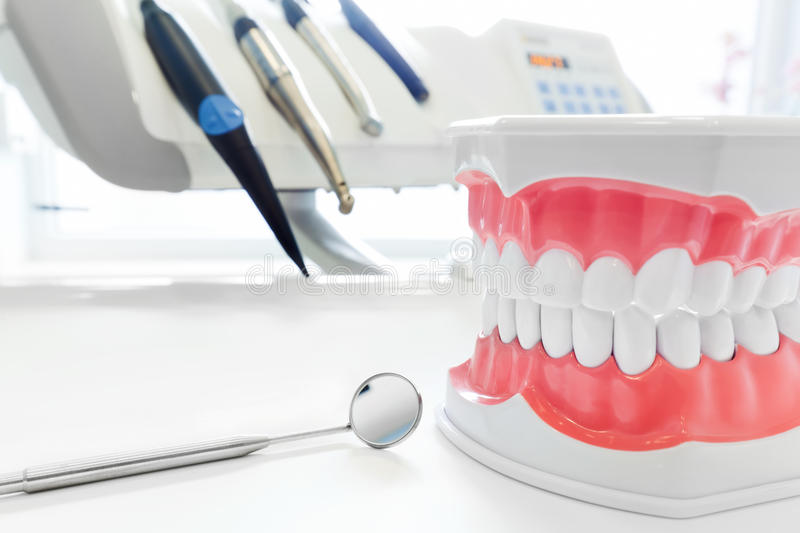 Clean teeth dental jaw model, mirror and dentistry instruments in dentist's office. royalty free stock images