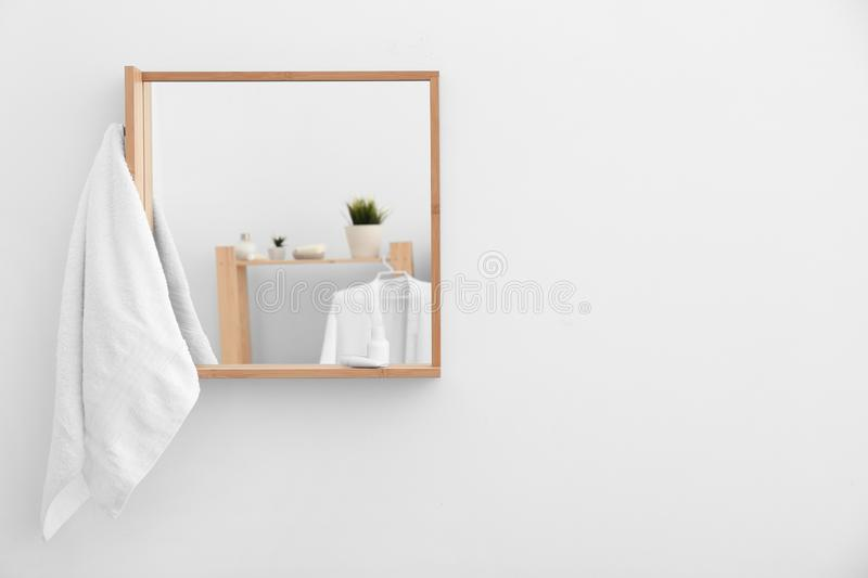 Clean terry towel and mirror on white wall indoors stock photos