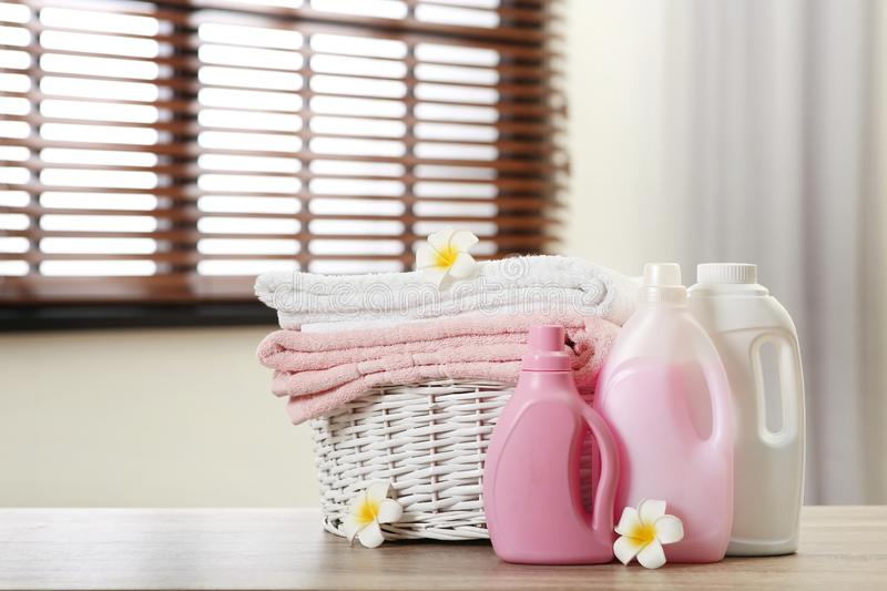 Clean towels in basket with flowers and detergents on table indoors. Space for text royalty free stock image